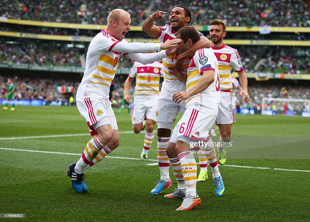 Shaun Maloney of Scotland is mobbed by team mates including Ikechi Anya and Steven Naismith (L) after scoring his goal during the UEFA EURO 2016 Qualifier Group D match between Republic of Ireland and Scotland at Aviva Stadium on June 13, 2015 in Dublin, Ireland.