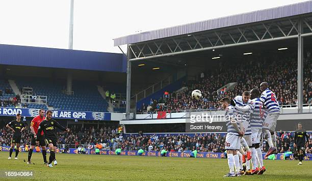 Shaun Maloney of Wigan Athletic scores the equalising goal from a free kick during the Barclays Premier League match between Queens Park Rangers and...
