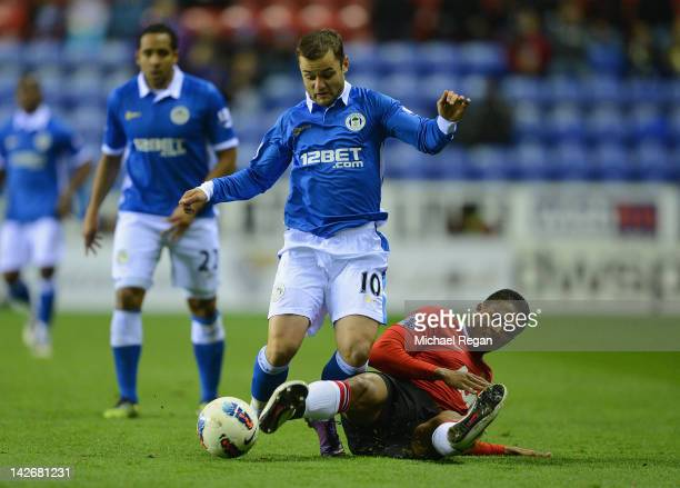 Shaun Maloney of Wigan battles Antonio Valencia of Man Utd during the Barclays Premier League match between Wigan Athletic and Manchester United at...