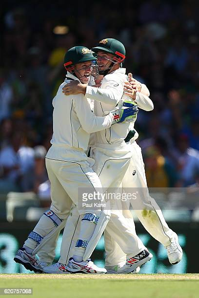 Shaun Marsh of Australia is congratulated by Peter Nevill and Steve Smith after taking a catch to dismiss Temba Bavuma of South Africa during day one...