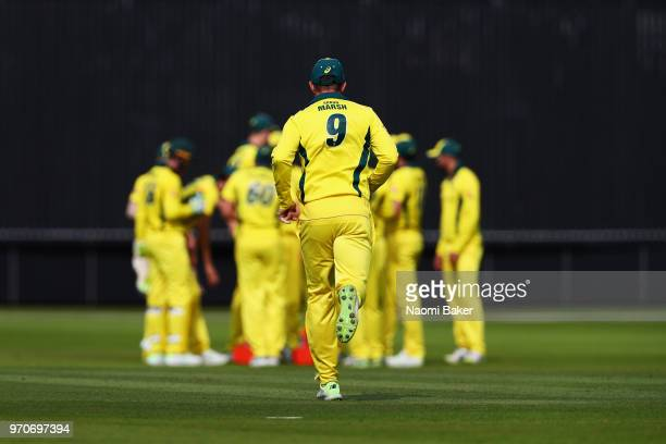 Shaun Marsh of Australia runs to join the celebrations of D'Arcy Short of Australia celebrating with teammates after dismissing Hilton Cartwright of...