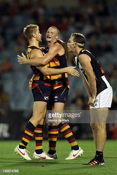 Shaun McKernan and Sam Jacobs of Adelaide celebrate as Nick Maxwell of the Magpies reacts during the round three NAB Cup match between the Adelaide...