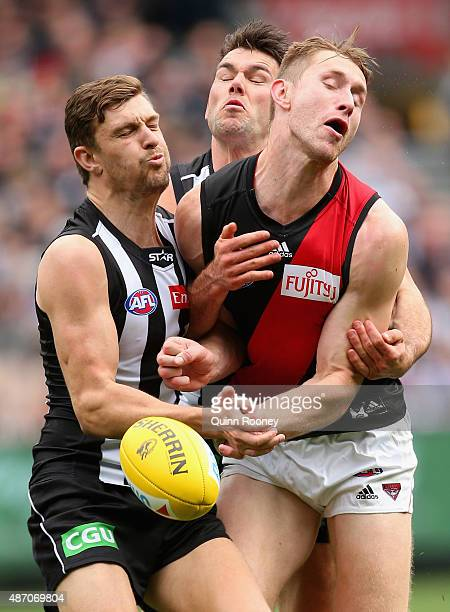 Shaun McKernan of the Bombers handballs whilst being tackled by Adam Oxley and Levi Greenwood of the Magpies during the round 23 AFL match between...