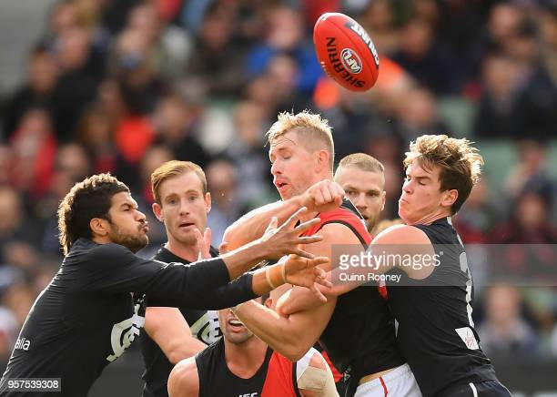 Shaun McKernan of the Bombers handballs whilst being tackled by Paddy Dow of the Blues during the round eight AFL match between the Carlton Blues and...