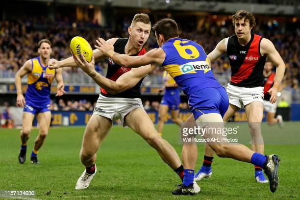 Shaun McKernan of the Bombers handpasses the ball under pressure from Elliot Yeo of the Eagles during the round 14 AFL match between the West Coast...