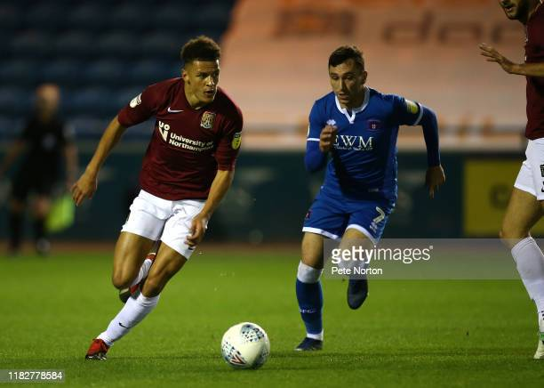Shaun McWilliams of Northampton Town moves forward with the ball away from Nathan Thomas of Carlisle United during the Sky Bet League Two match...