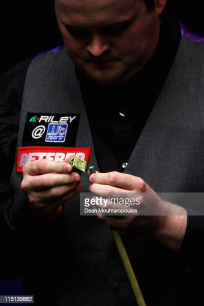 Shaun Murphy of England chalks his cue in the round two game against Ronnie O'Sullivan of England during day nine of the Betfredcom World Snooker...