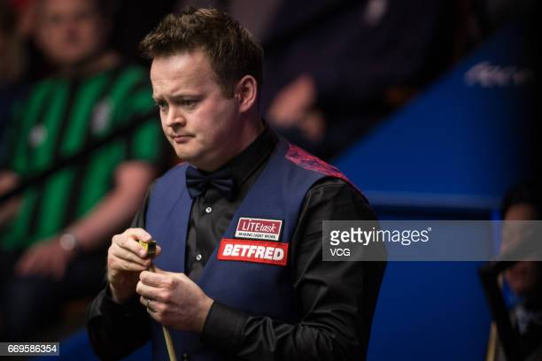 Shaun Murphy of England chalks the cue during his first round match against Yan Bingtao of China on day three of Betfred World Championship 2017 at...