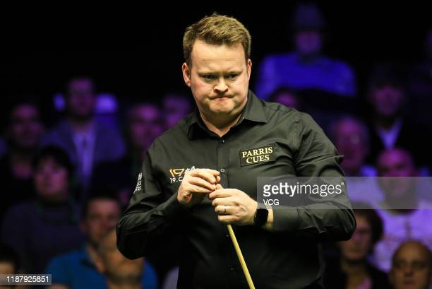 Shaun Murphy of England chalks the cue during the quarter-final match against Ronnie O'Sullivan of England on day five of 2019 Northern Ireland Open...