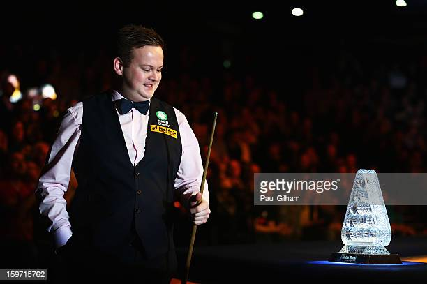 Shaun Murphy of England looks at The Masters Trophy as he walks out for the semifinal match between Neil Robertson of Australia and Shaun Murphy of...