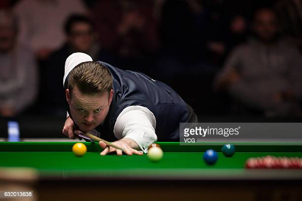 Shaun Murphy of England plays a shot during his first round match against Barry Hawkins of England on day four of the Dafabet Masters at Alexandra...