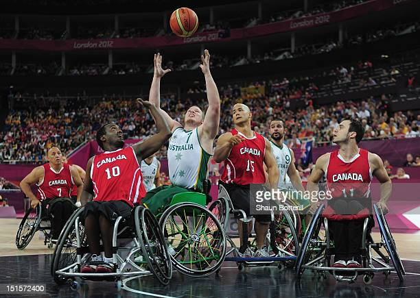 Shaun Norris of Australia is challenged by Abdi Dini and David Eng of Canada during the gold medal Wheelchair Basketball match between Australia and...