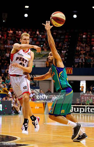 Shaun Redhage of the Wildcats passes the ball past Michael Cedar of the Crocodiles during the round two NBL match between the Townsville Crocodiles...