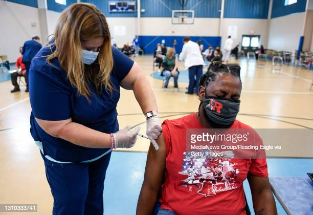 Shaun Richardson is given a dose of COVID-19 vaccine by nurse Elizabeth Johnson. At the Olivet Boys and Girls Club Pendora site in Reading,...