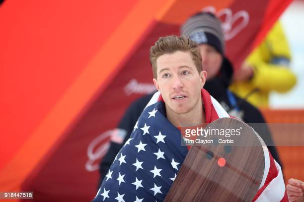 Shaun White of the United States celebrates with the American flag after winning the gold medal in the Snowboard Men's Halfpipe competition at...