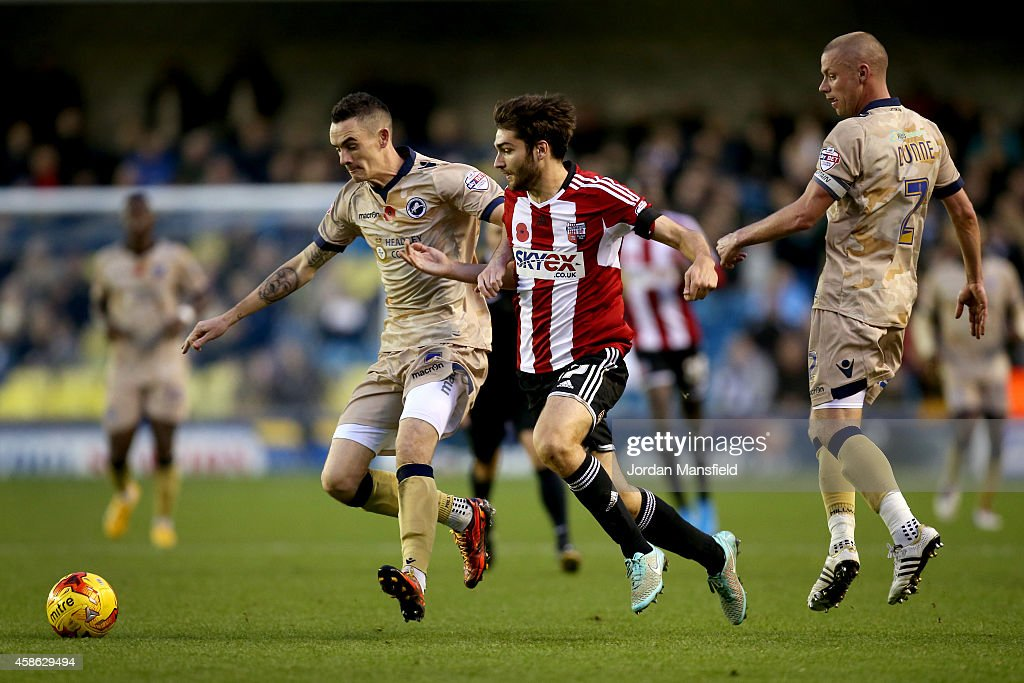 Shaun Williams of Millwall and Jon Toral of Brentford tackle for the ball during the Sky Bet Championship match between Millwall and Brentford at The Den on November 8, 2014 in London, England.