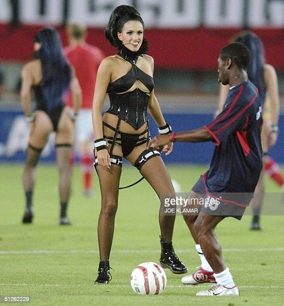 Shaun Wright-Phillips of England stops a ball during the warm-up near a dancer of musical group Barbarella performing shortly before the beggining of...