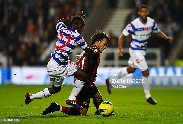 Shaun Wright-Phillips of Queens Park Rangers challenges David Silva of Manchester City during the Barclays Premier League match between Queens Park...