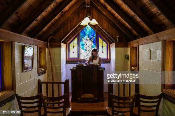 "Shauna Swain Riggs writes her prayers inside the ""Smallest Church In America"" in Townsend, Georgia, amid the novel coronavirus pandemic on April 26,..."