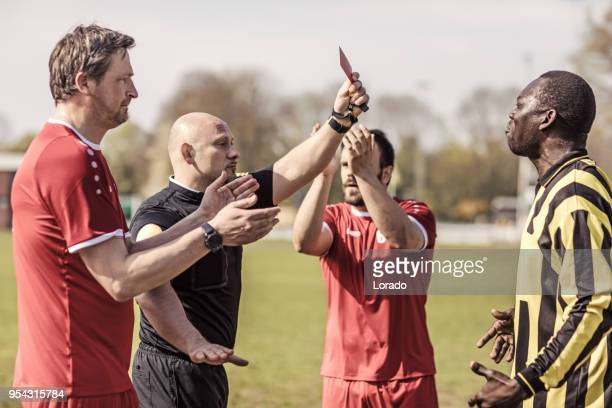 shaved handsome caucasian male soccer referee during a football match - yellow card stock pictures, royalty-free photos & images