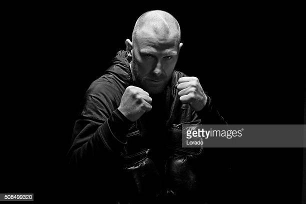 Shaved male fighter posing with boxing gloves and clenched fists