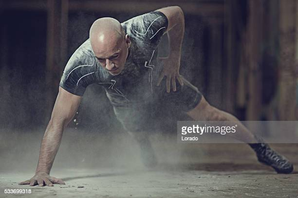 Shaven headed male athlete training in abandoned warehouse