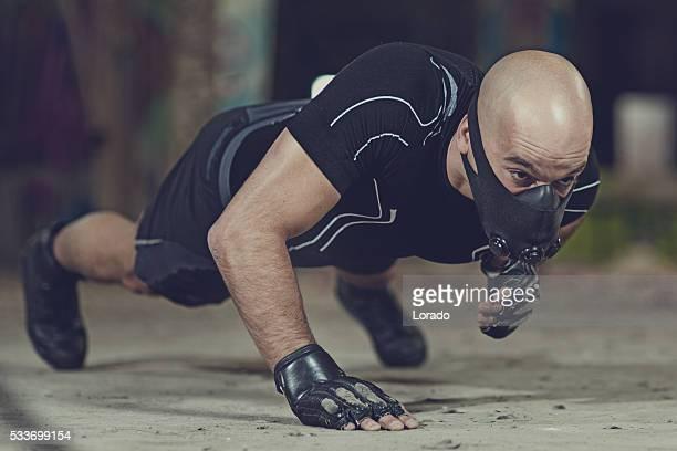 Barbeado cabeça masculino atleta formação em armazém com aparelho de protecção respiratória