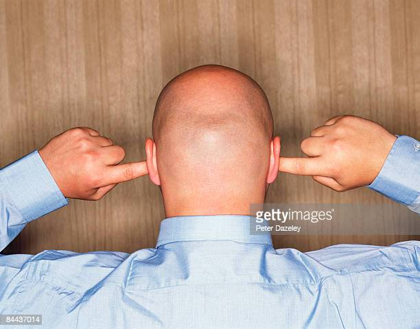 shaven headed man with fingers in ears - fingers in ears stock pictures, royalty-free photos & images