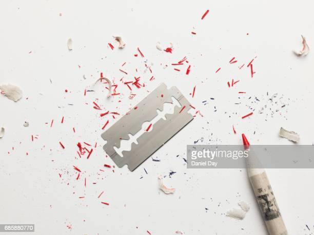 shaving blade with red pencil shavings representing being cut / blood - self harm stock photos and pictures