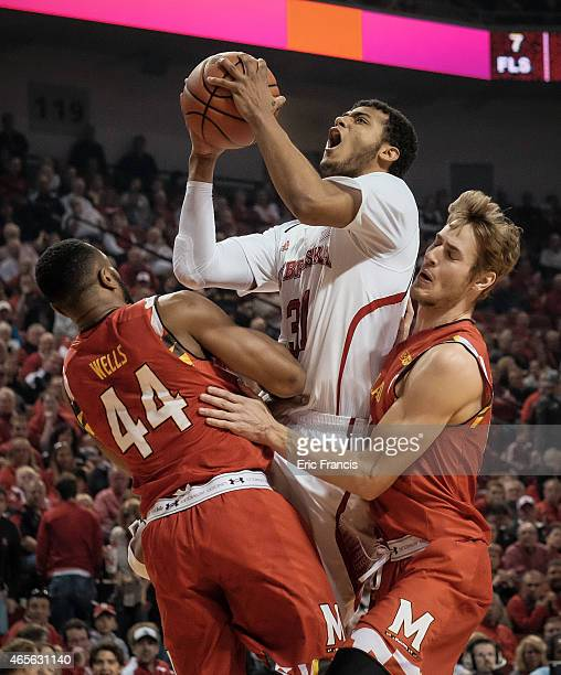 Shavon Shields of the Nebraska Cornhuskers drives to the basket against Dez Wells and Jake Layman of the Maryland Terrapins during their game at...