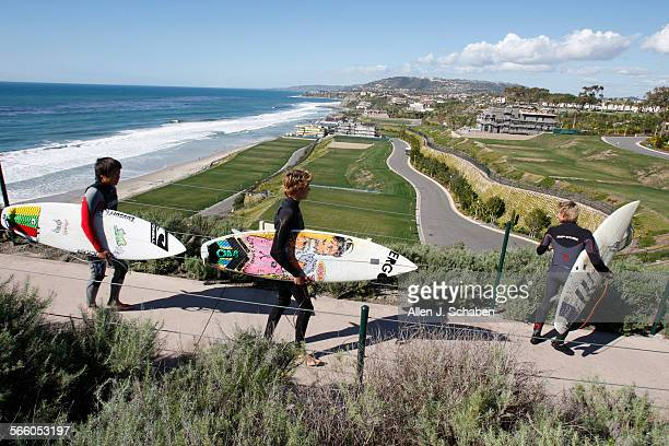 Shaw Kobayashi left, Dylan Stratton center, and Gulo Simon right, all of San Clemente, walk down a paved path from the bluff past The Strand at...