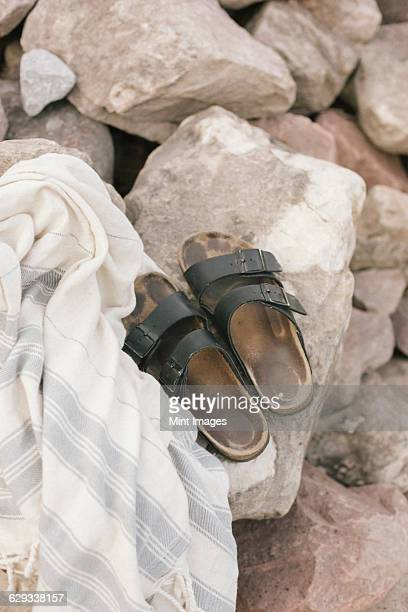 A shawl and pair of sandals on a rock.