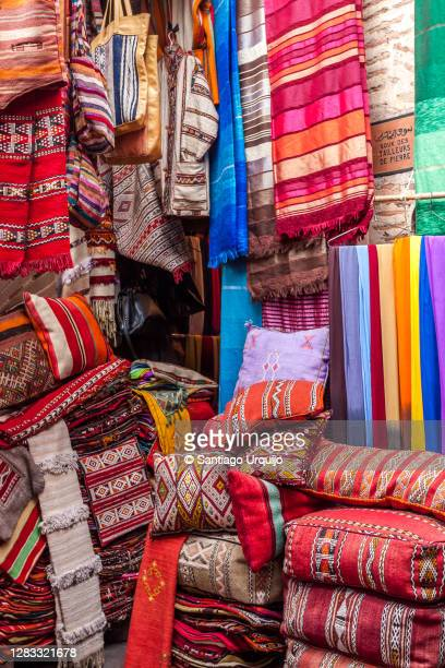 shawls and cushions for sale at the bazaar - bazaar stockfoto's en -beelden