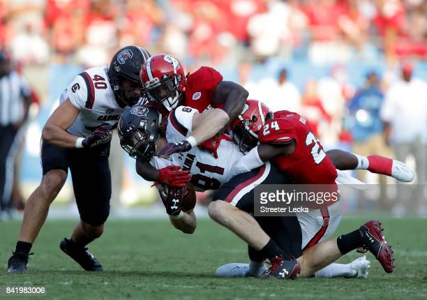 Shawn Boone of the North Carolina State Wolfpack stops Hayden Hurst of the South Carolina Gamecocks during their game at Bank of America Stadium on...