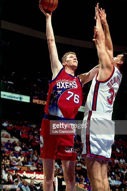 Shawn Bradley of the Philadelphia 76ers shoots a hook shot against Duane Schintzius of the New Jersey Nets during a game at the Brendan Byrne Arena...