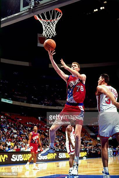 Shawn Bradley of the Philadelphia 76ers shoots a layup against Duane Schintzius of the New Jersey Nets during a game at the Brendan Byrne Arena on...