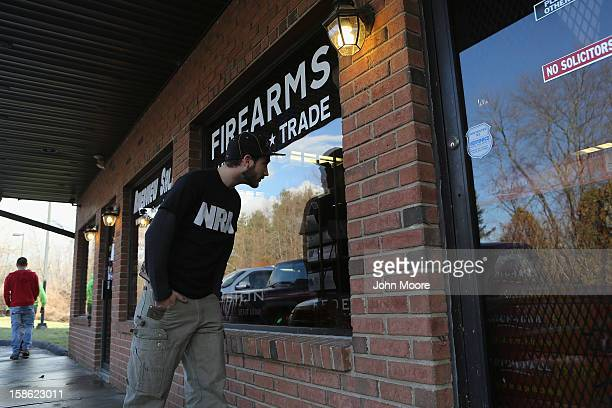 Shawn Cavana a member of the NRA who says he personally owns an AR15 semiautomatic rifle looks into the closed Riverview Gun Sales shop while gun...
