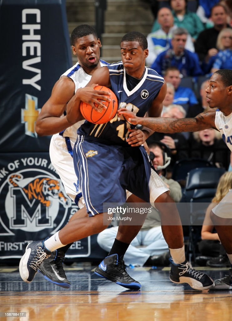 Shawn Glover #11 of the Oral Roberts Golden Eagles drives between Adonis Thomas #4 and Antonio Barton #2 of the Memphis Tigers on December 28, 2012 at FedExForum in Memphis, Tennessee.