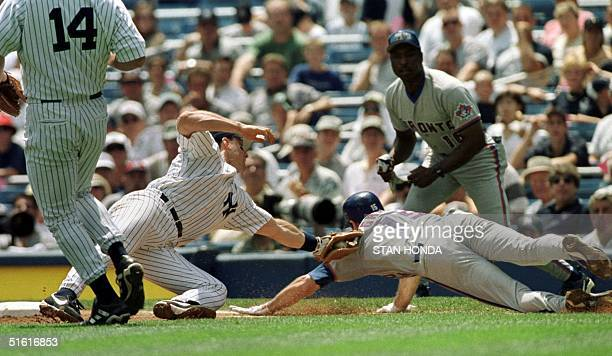 Shawn Green of the Toronto Blue Jays is tagged out by New York Yankees first baseman Tino Martinez in first inning of their game 04 August 1999 at...