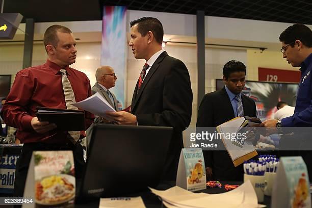 Shawn Holman speaks to Robert Allen a recruiter for IHOP restaurants during the JobNewsUSA job fair at the BBT Center on November 15 2016 in Sunrise...