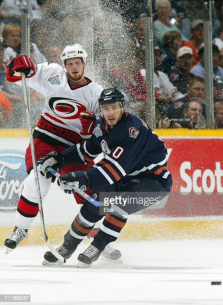 Shawn Horcoff of the Edmonton Oilers and Eric Staal of the Carolina Hurricanes fight for control of the puck during game four of the 2006 NHL Stanley...