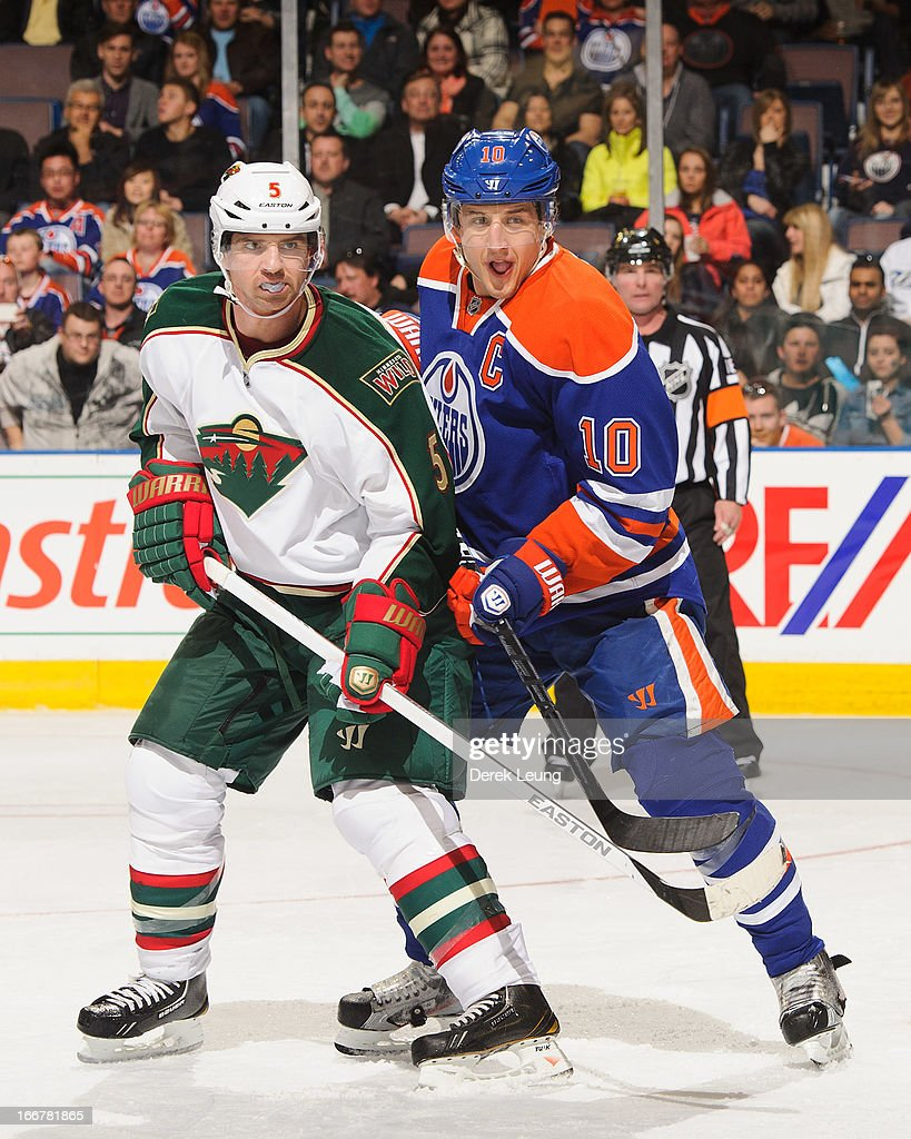 Shawn Horcoff #10 of the Edmonton Oilers battles for position against Brett Clark #5 of the Minnesota Wild during an NHL game at Rexall Place on April 16, 2013 in Edmonton, Alberta, Canada.