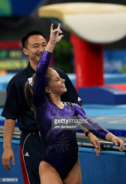 Shawn Johnson of the United States reacts with her coach Liang Chow behind her after finsihing her floor routine during the women's individual floor...