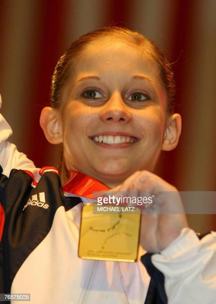 Shawn Johnson of the US presents her gold medal on the podium after winning the women's individual all-around final of the 40th World Artistic...