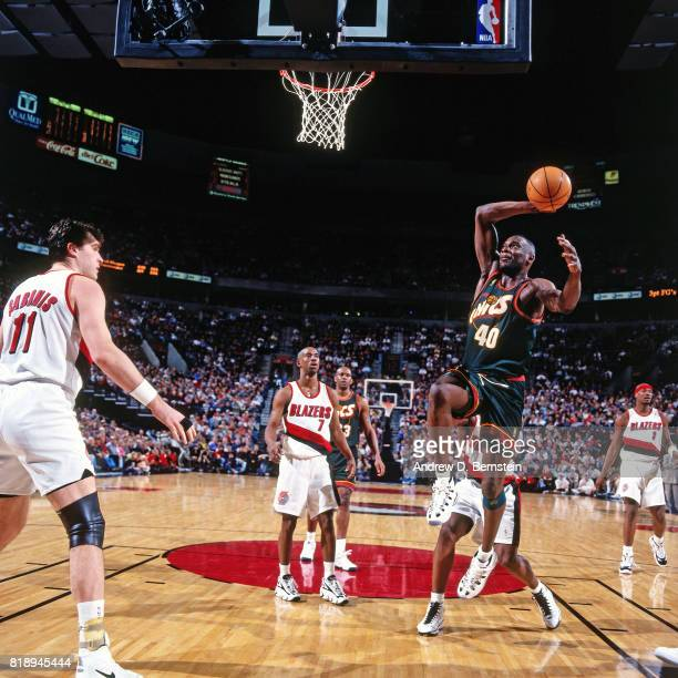 Shawn Kemp of the Seattle SuperSonics dunks against Arvydas Sabonis of the Portland Trail Blazers during a game at the Rose Garden Arena in Portland...