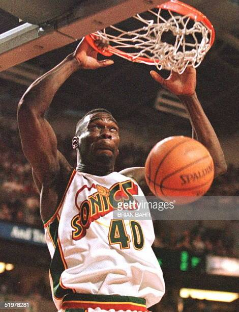 Shawn Kemp of the Seattle SuperSonics hangs on the rim after his dunk 12 June during the first quarter of game four of the NBA Finals against the...