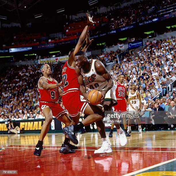 Shawn Kemp of the Seattle SuperSonics makes a move to the basket against John Salley and Dennis Rodman of the Chicago Bulls in Game Three of the 1996...