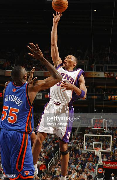 Shawn Marion of the Phoenix Suns shoots against Dikembe Mutombo of the New York Knicks on February 25 2004 at America West Arena in Phoenix Arizona...