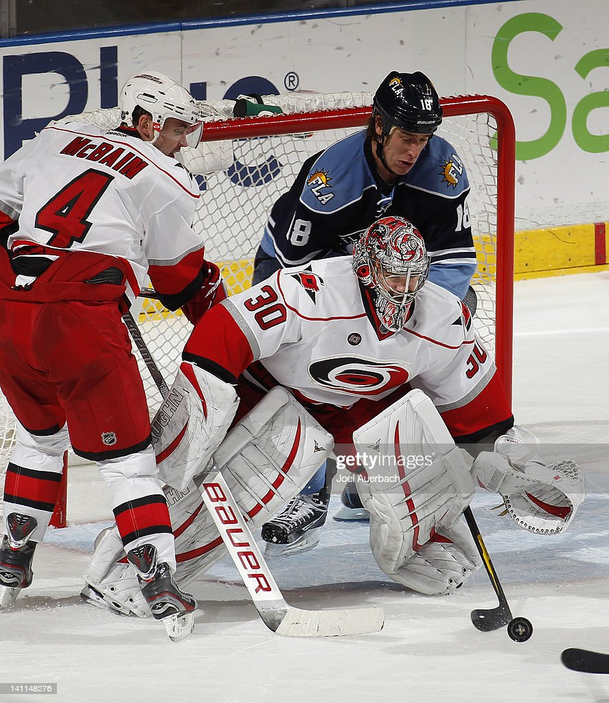 Shawn Matthias #18 of the Florida Panthers slips in behind goaltender Cam Ward #30 of the Carolina Hurricanes as he makes a save on March 11, 2012 at the BankAtlantic Center in Sunrise, Florida. The Panthers defeated the Hurricanes 2-0.