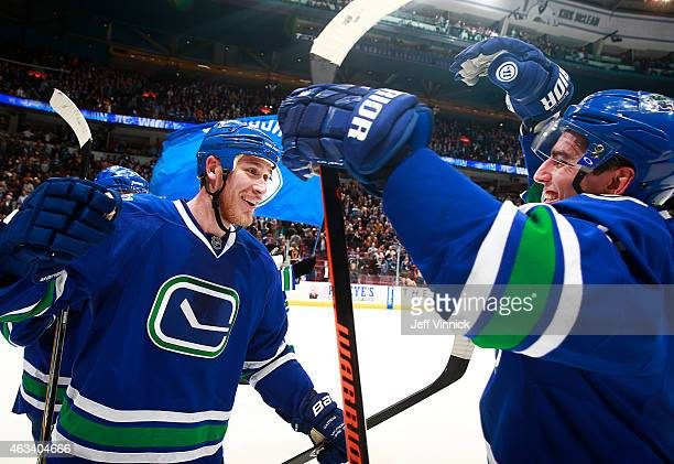 Shawn Matthias of the Vancouver Canucks is congratulated by Alexandre Burrows after scoring a hat trick against the Boston Bruins during their NHL...